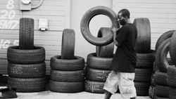 A man works across the street at a tire repair shop.
